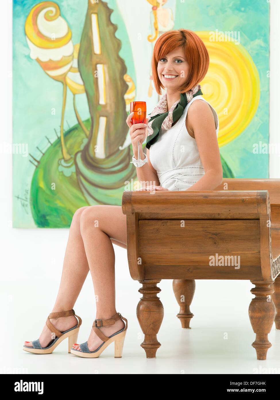 Close-up of young attractive happy woman sitting in an art gallery, tenant un verre rouge champane, avec des œuvres d'art colorées en arrière-plan Banque D'Images