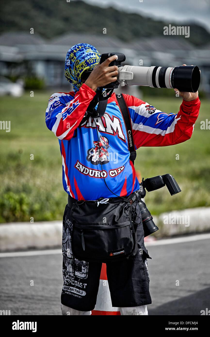 Attired coloré photographe de sport professionnel prise de photos avec un assortiment de caméras et objectifs Canon. Photo Stock