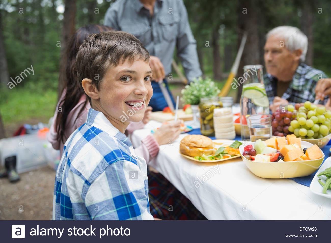 Portrait of boy avoir votre repas en famille au camping Photo Stock