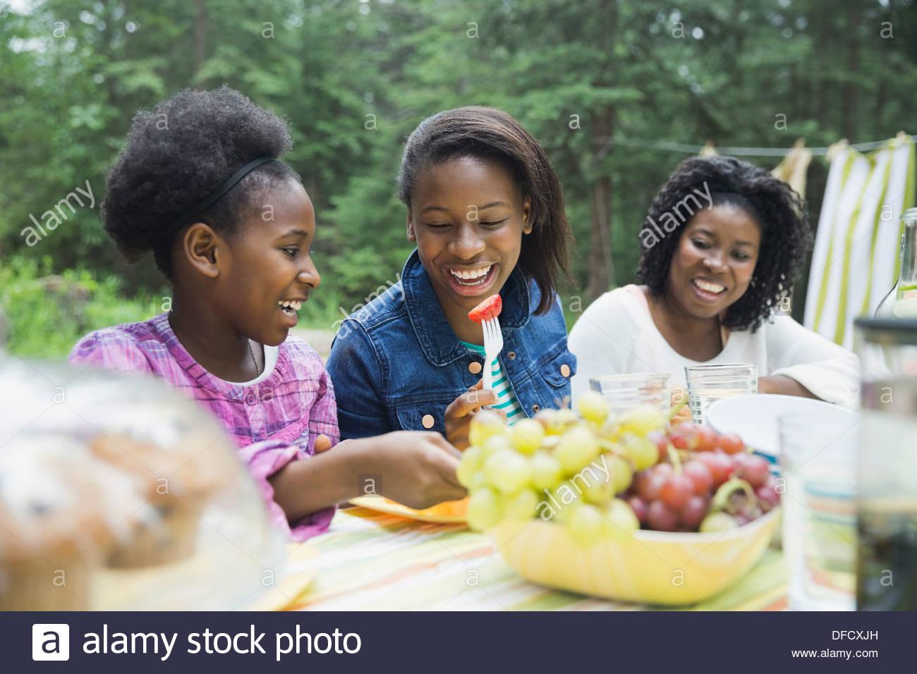 Frères et soeurs gais ayant repas avec mère au camping Photo Stock