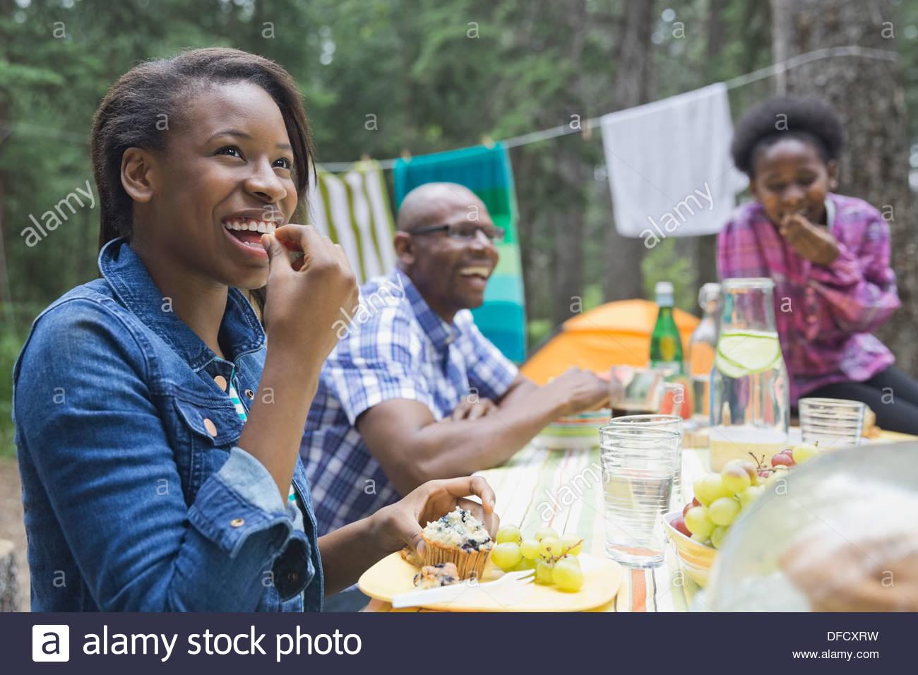 Happy girl avoir votre repas en famille au camping Photo Stock