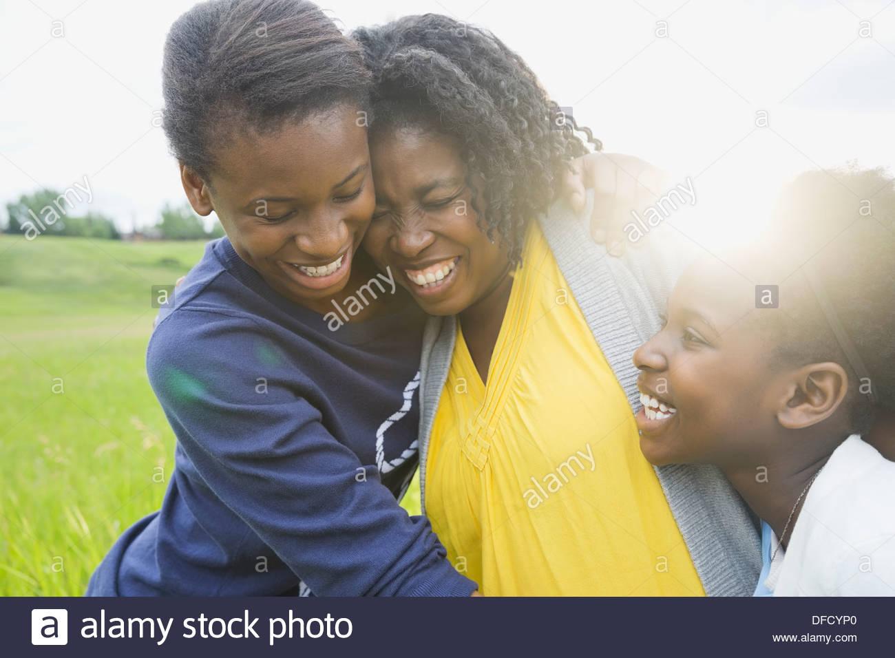 La mère et les filles joyeuses accolades à l'extérieur Photo Stock