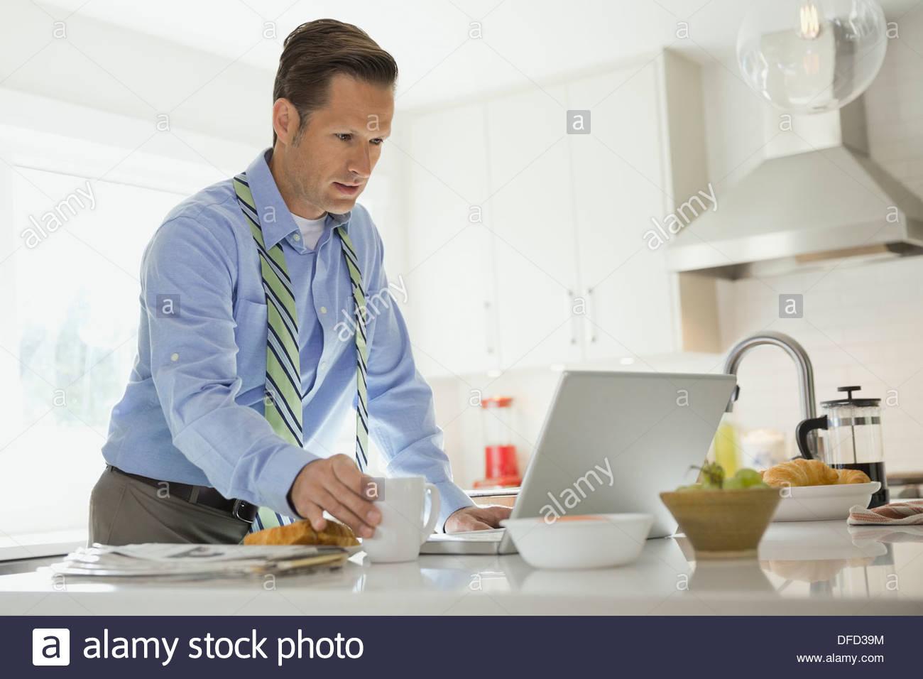 Mature businessman using laptop in cuisine domestique Photo Stock
