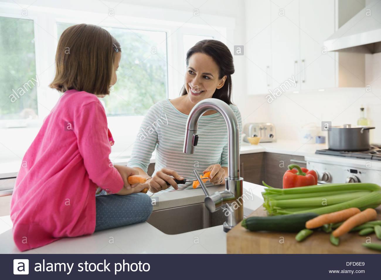 Mère et fille l'épluchage des carottes dans la cuisine Photo Stock