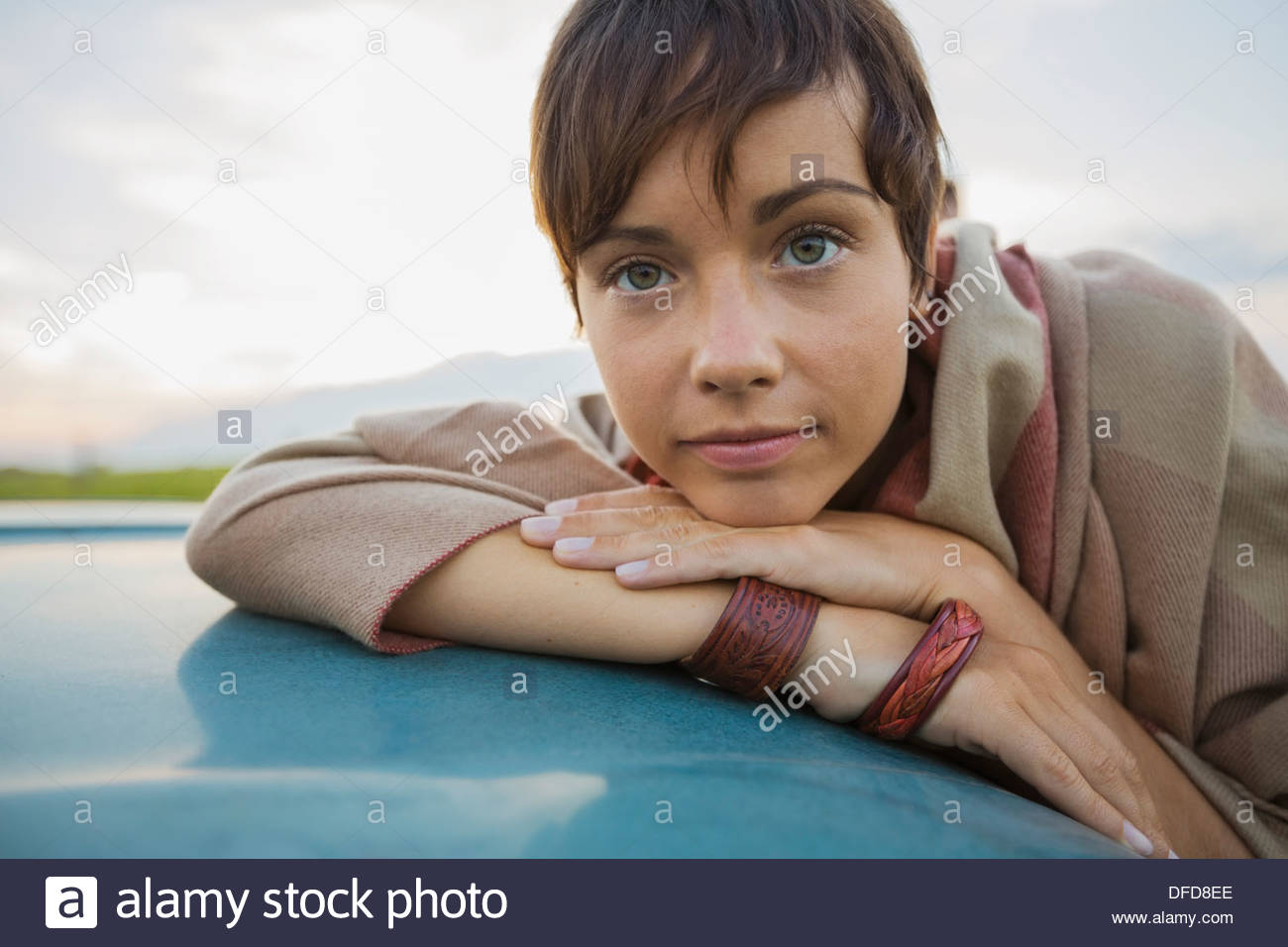 Portrait of young woman resting head on hands Banque D'Images
