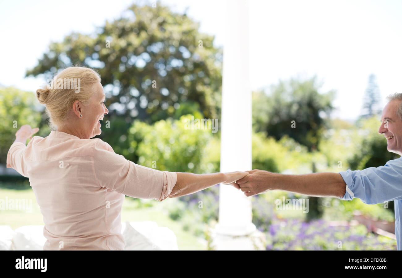 Senior couple dancing on patio Photo Stock