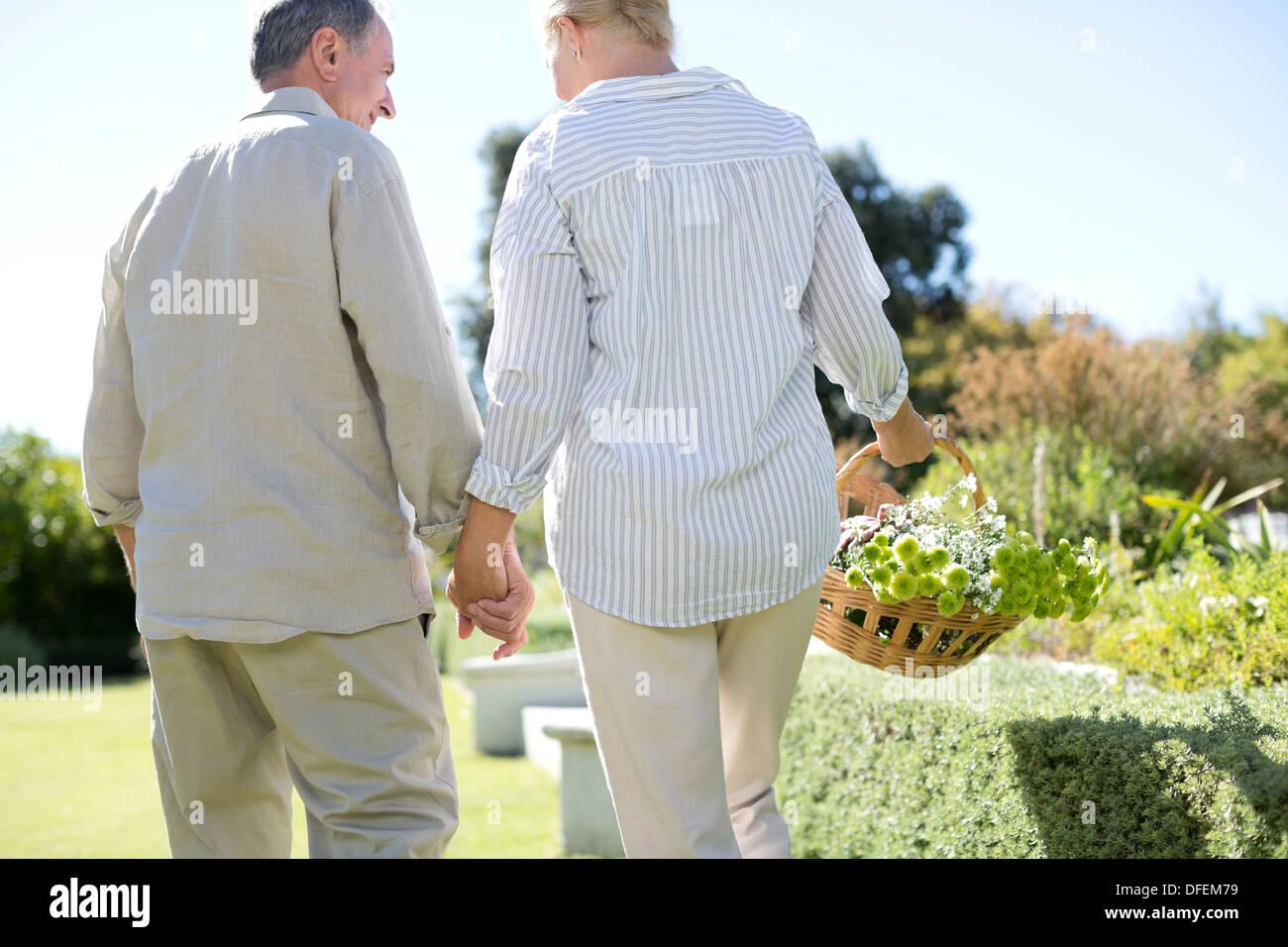 Senior couple holding hands in garden Photo Stock