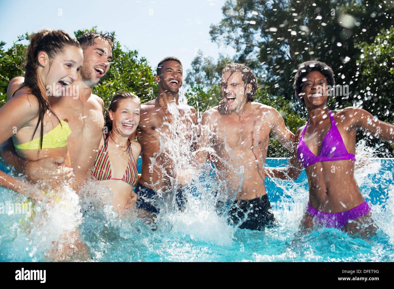 Amis jouant dans une piscine Photo Stock