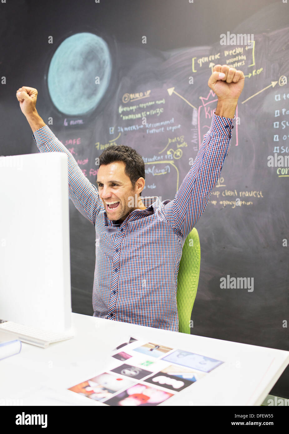 Businessman cheering at desk in office Banque D'Images
