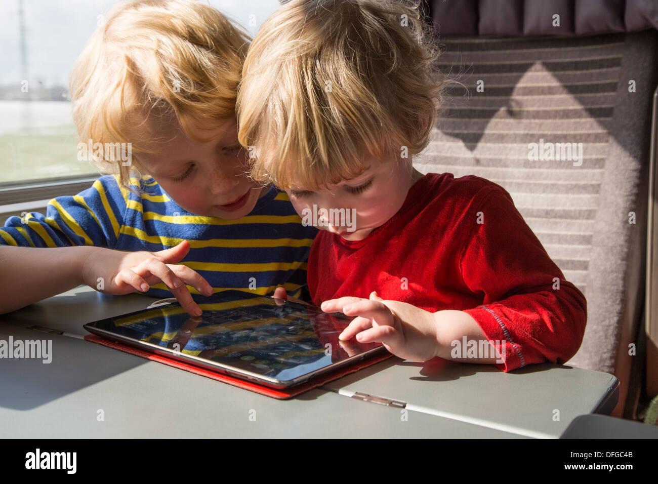 Deux frères jouant sur un iPad Photo Stock