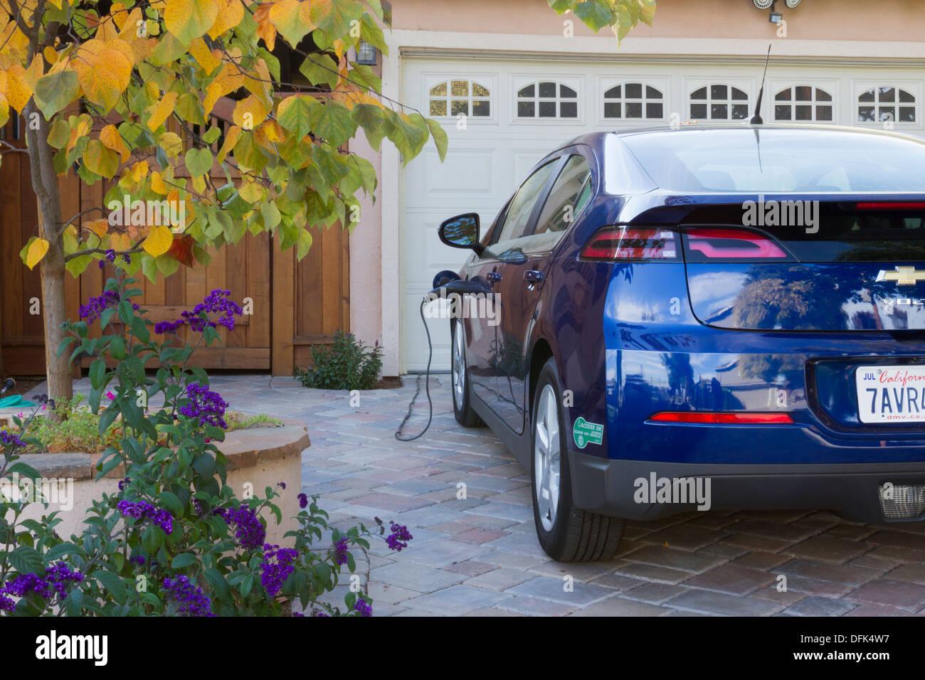 Plug-in voiture électrique avec autocollant de covoiturage parqué dans l'allée, avec le connecteur branché et de charge à la maison Photo Stock