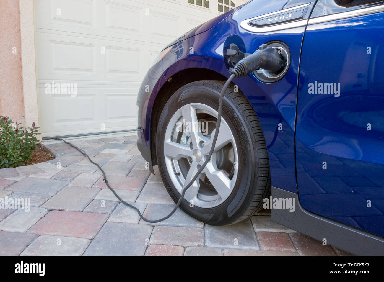 Chevrolet Volt plug-in voiture électrique avec le connecteur branché en charge, à la maison dans une entrée Photo Stock