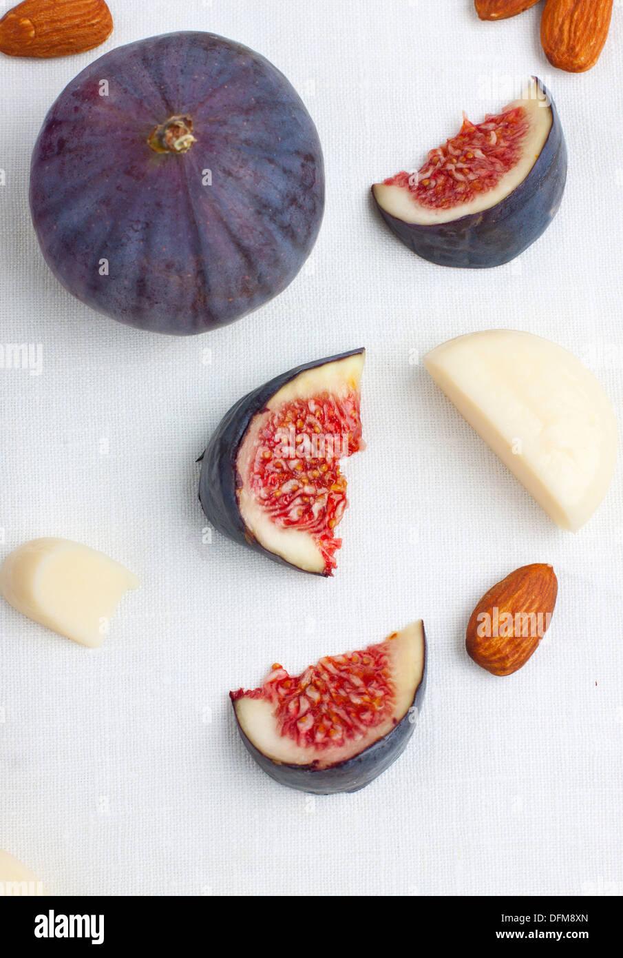 Figues fraîches coupées avec des tranches de fromage et quelques écrous Photo Stock