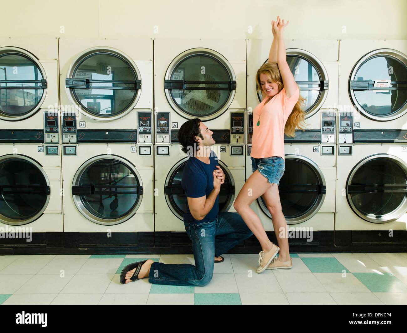 Un jeune homme s'agenouille devant une belle femme à San Diego coin laverie. Photo Stock