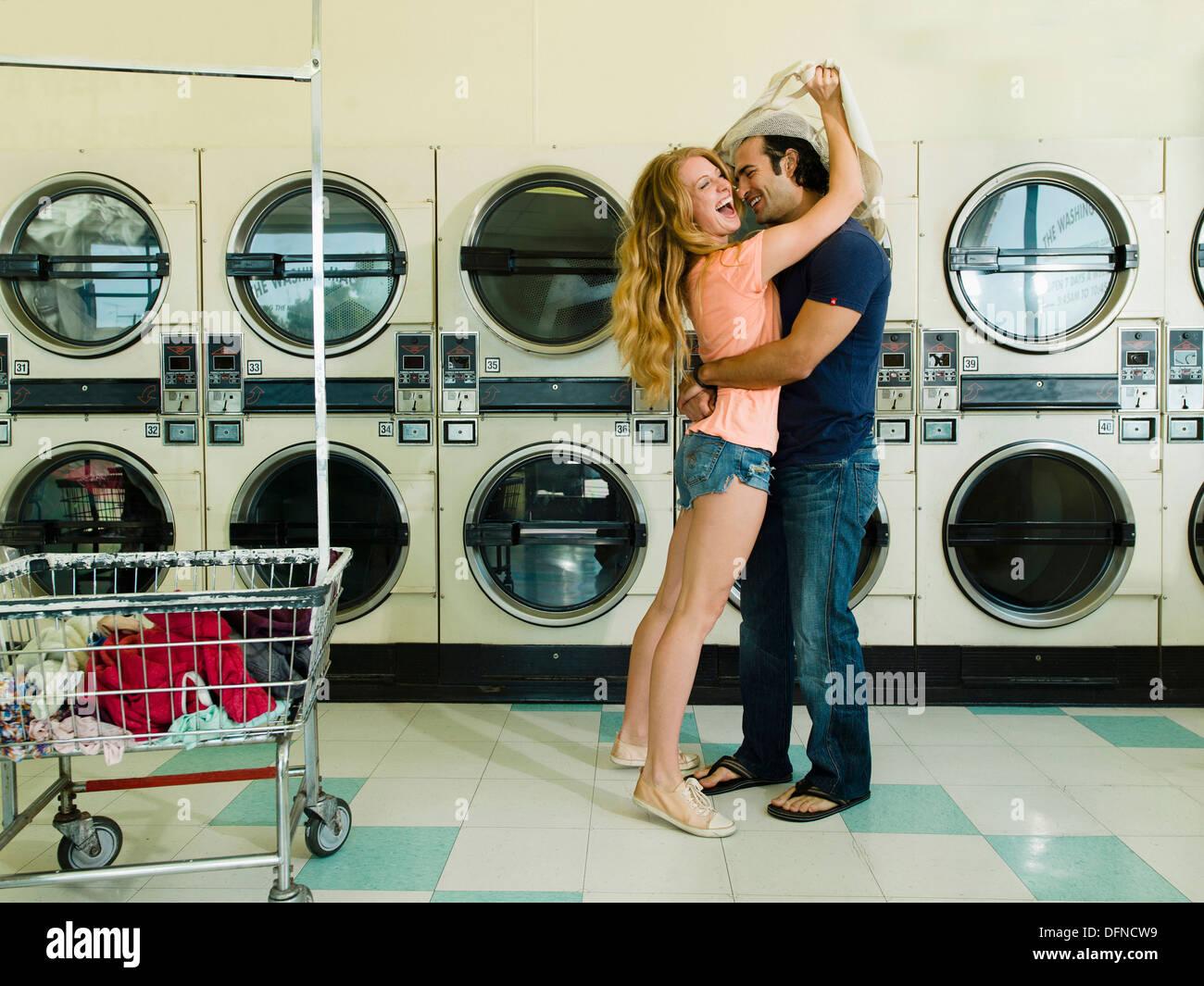 Un jeune homme épouse une belle femme à San Diego coin laverie. Photo Stock