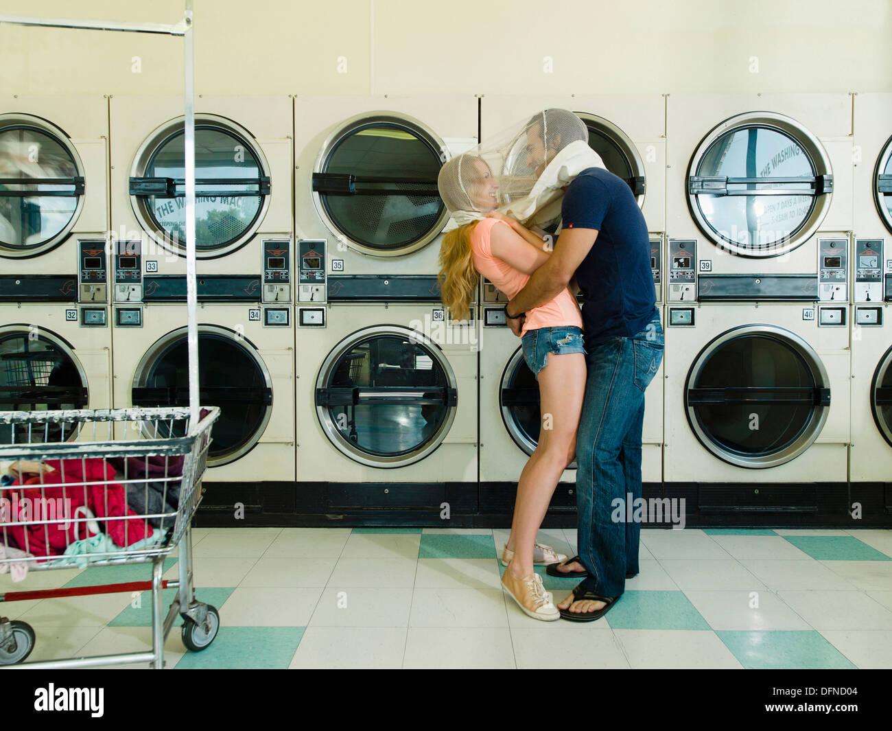 Une jolie femme hugs par un jeune homme à San Diego coin laverie. Photo Stock