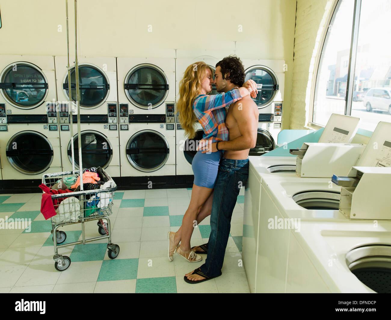 Une jolie femme en étreignant un corps nu jeune homme à San Diego coin laverie. Photo Stock