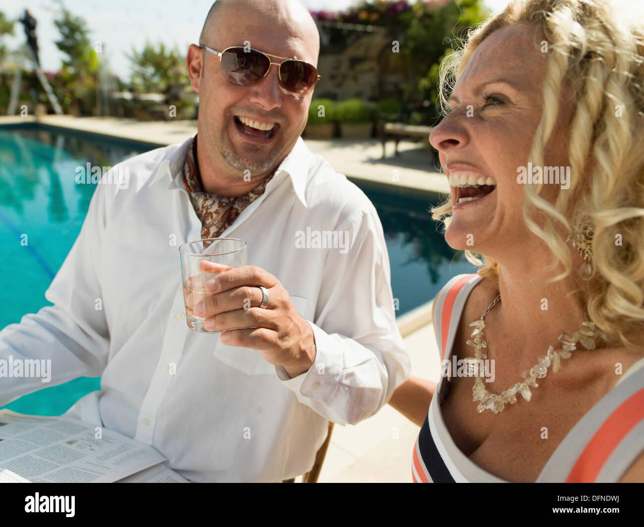 Un jeune homme aime son verre avec une belle femme par le côté d'une piscine à San Diego. Photo Stock