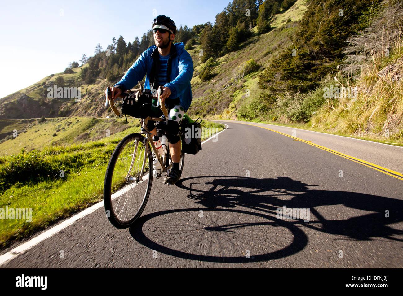 Un homme chevauche son vélo randonnée cycliste le long de la côte du Pacifique l'Autoroute Près de Jenner, en Californie. Photo Stock