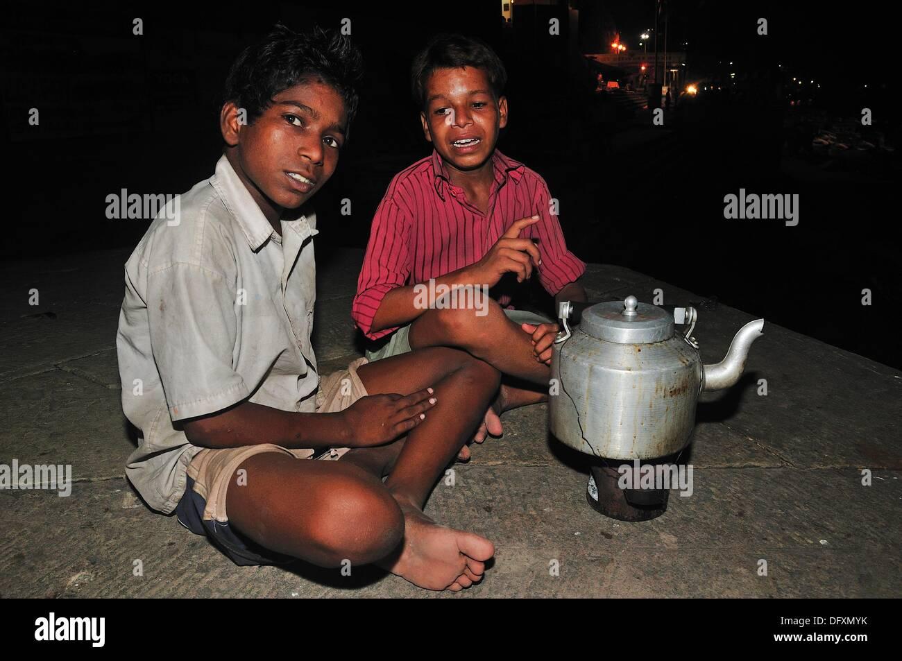 Jeunes Frères vendre post card dans la journée en fin d'après-midi vend des fleurs pour les pèlerins dans la nuit vend du thé chaud dans le noir Photo Stock