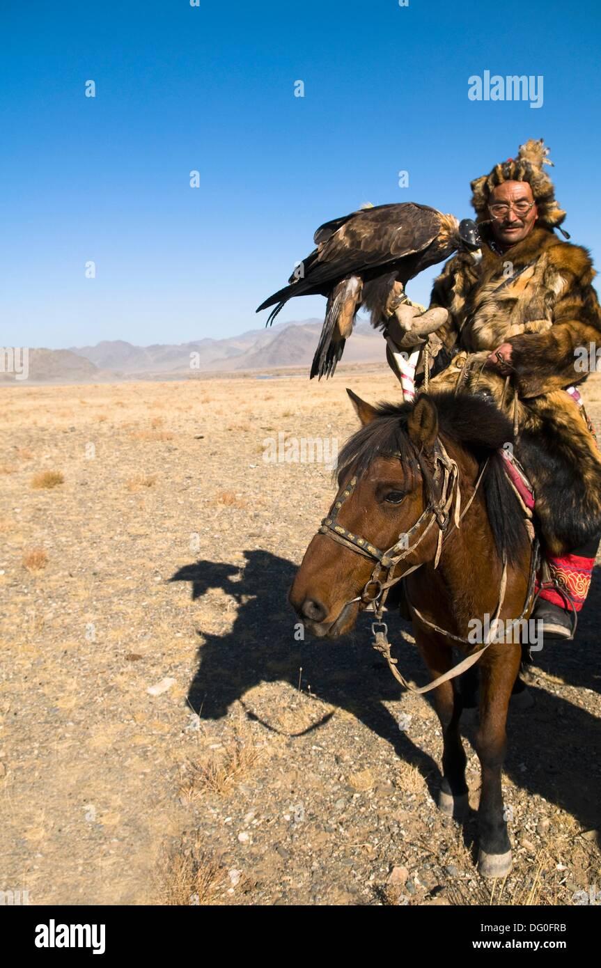Un eagle Hunter de la région de l'Altaï de Mongolie occidentale équitation son cheval. Banque D'Images