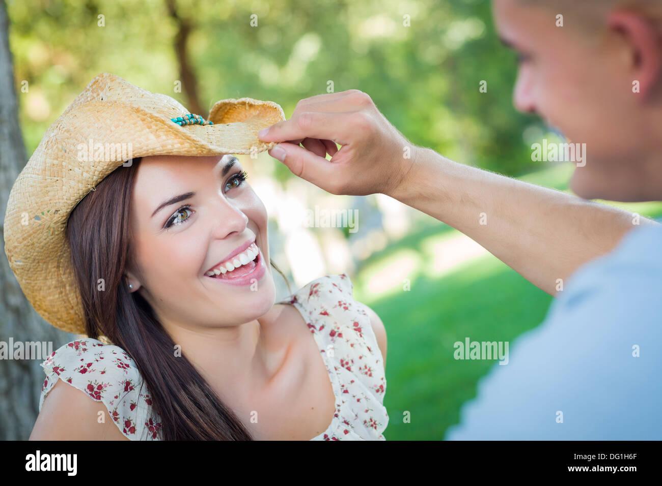 Happy Mixed Race couple romantique avec Cowboy Hat flirter dans le parc. Photo Stock