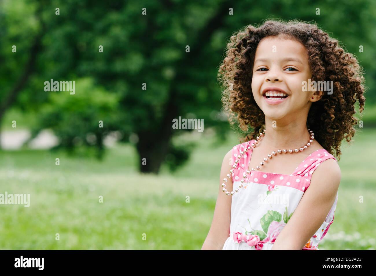 Souriante jeune fille aux cheveux bruns bouclés, Portrait Photo Stock
