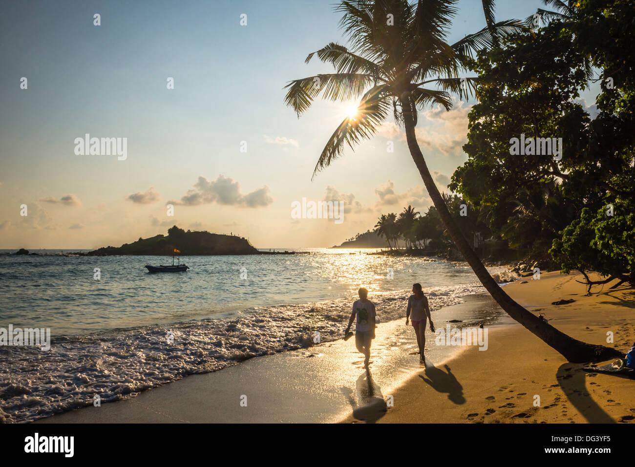 La plage de Mirissa, couple en prenant une promenade romantique sous un palmier au coucher du soleil, la Côte Sud, Sri Lanka, Asie Photo Stock