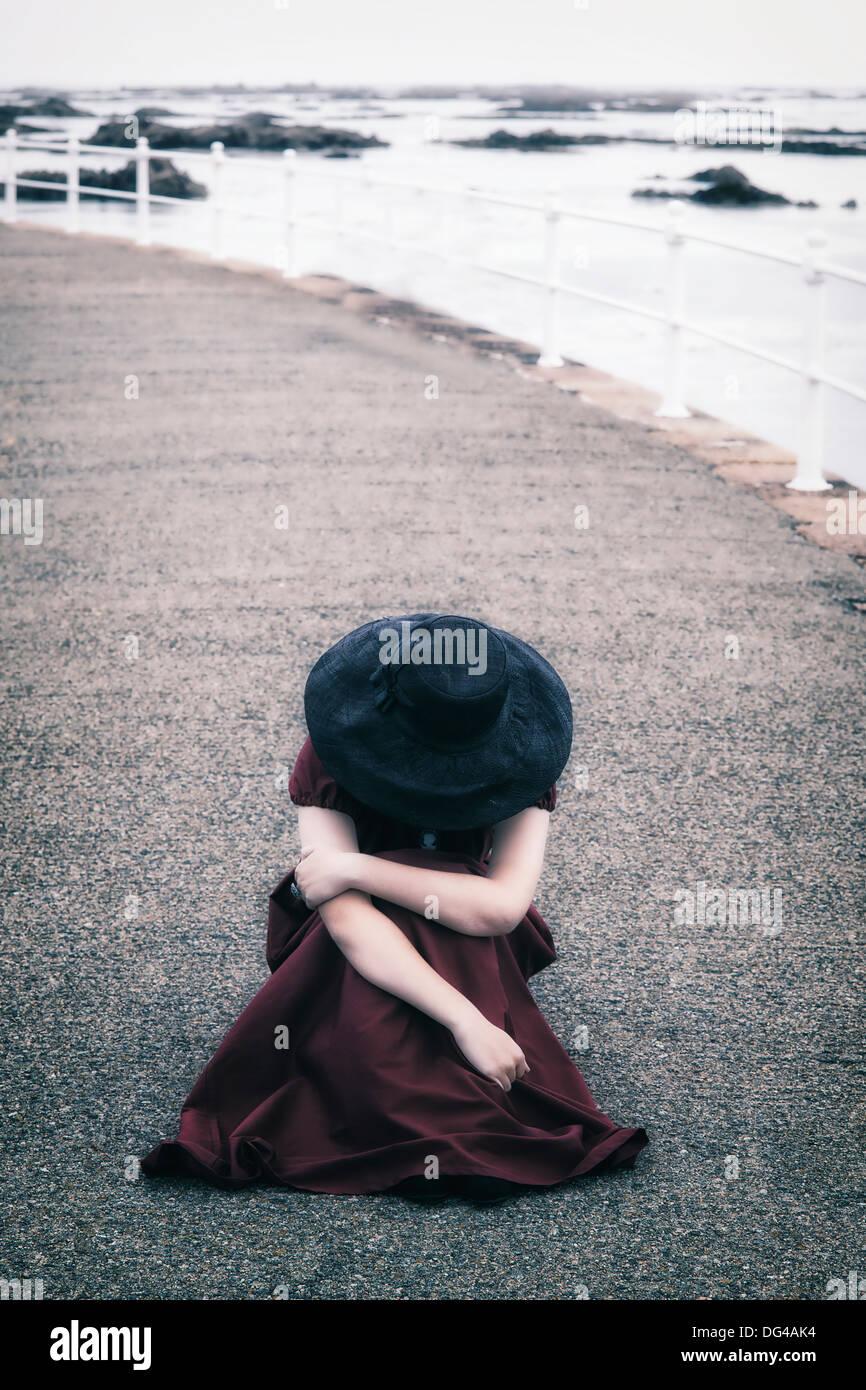 Une femme dans une robe rouge avec un chapeau noir est assis sur un quai Photo Stock