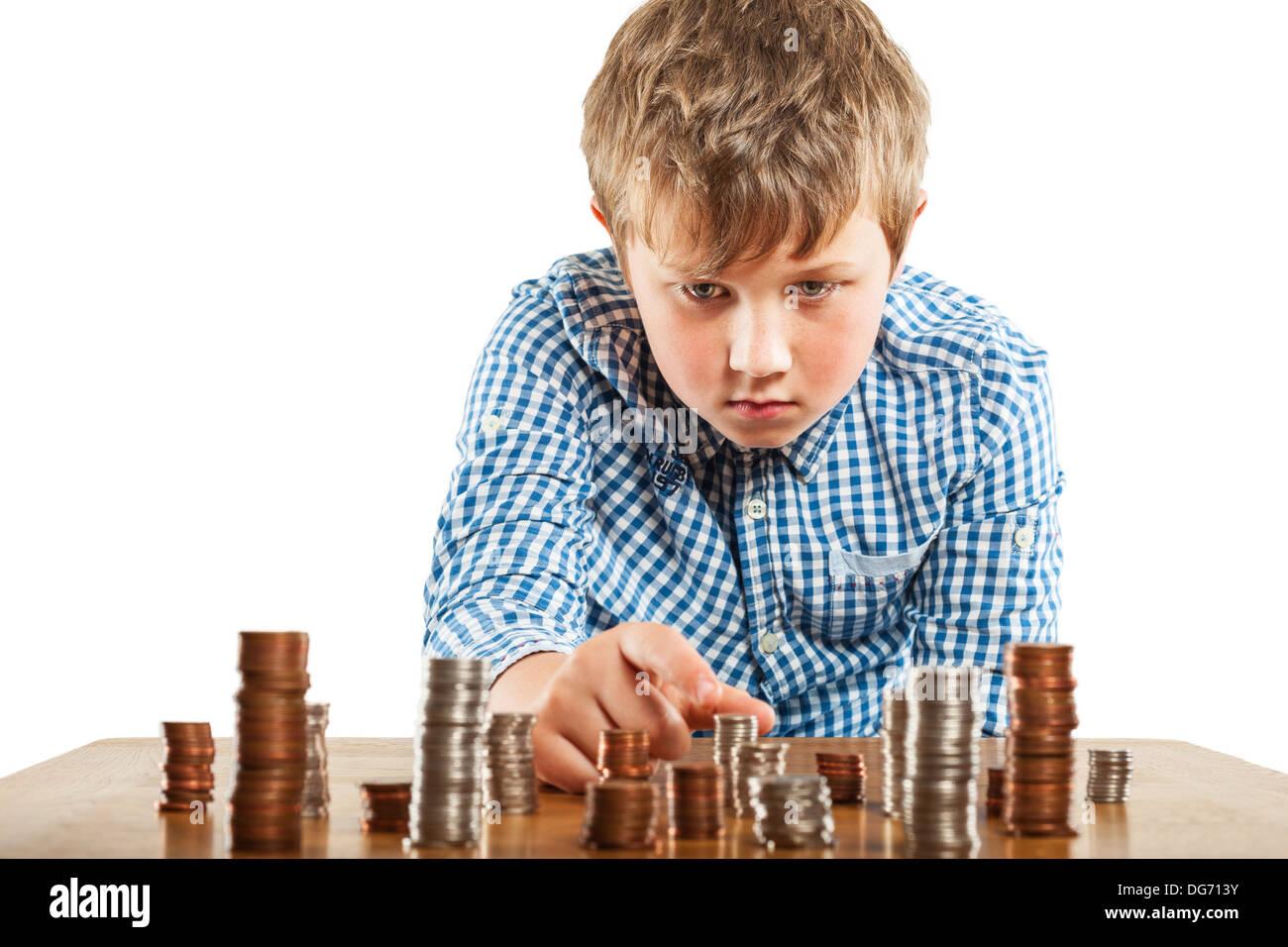 Un jeune garçon de 10 chefs son argent et les empile vers le haut Photo Stock