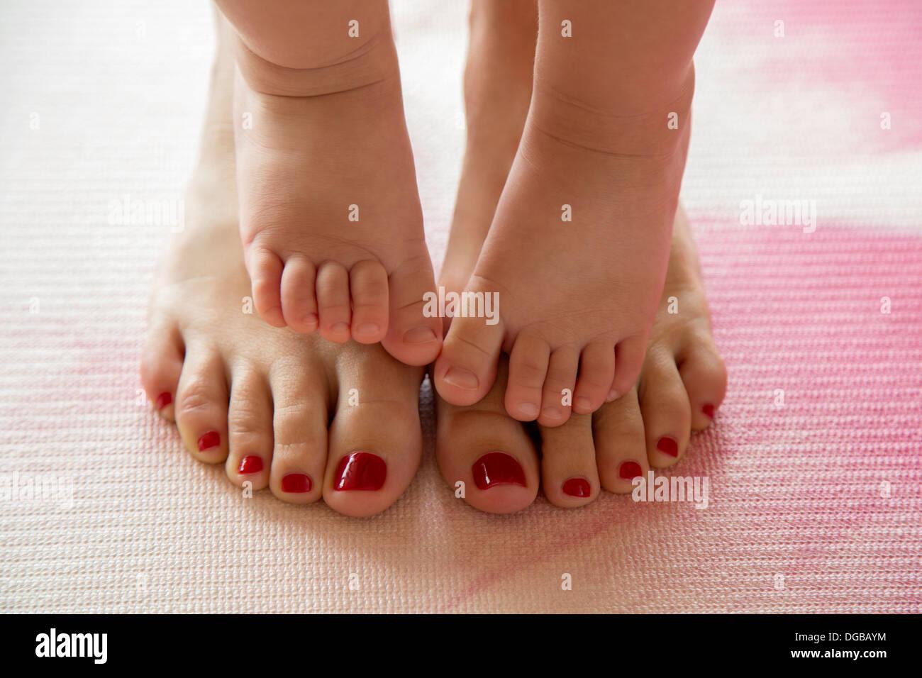 Les orteils de bébé sur les pieds de sa mère Photo Stock