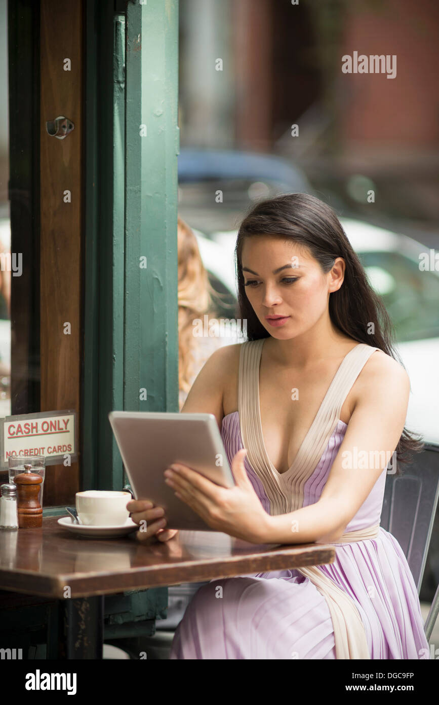 Woman using digital tablet in pavement cafe Photo Stock