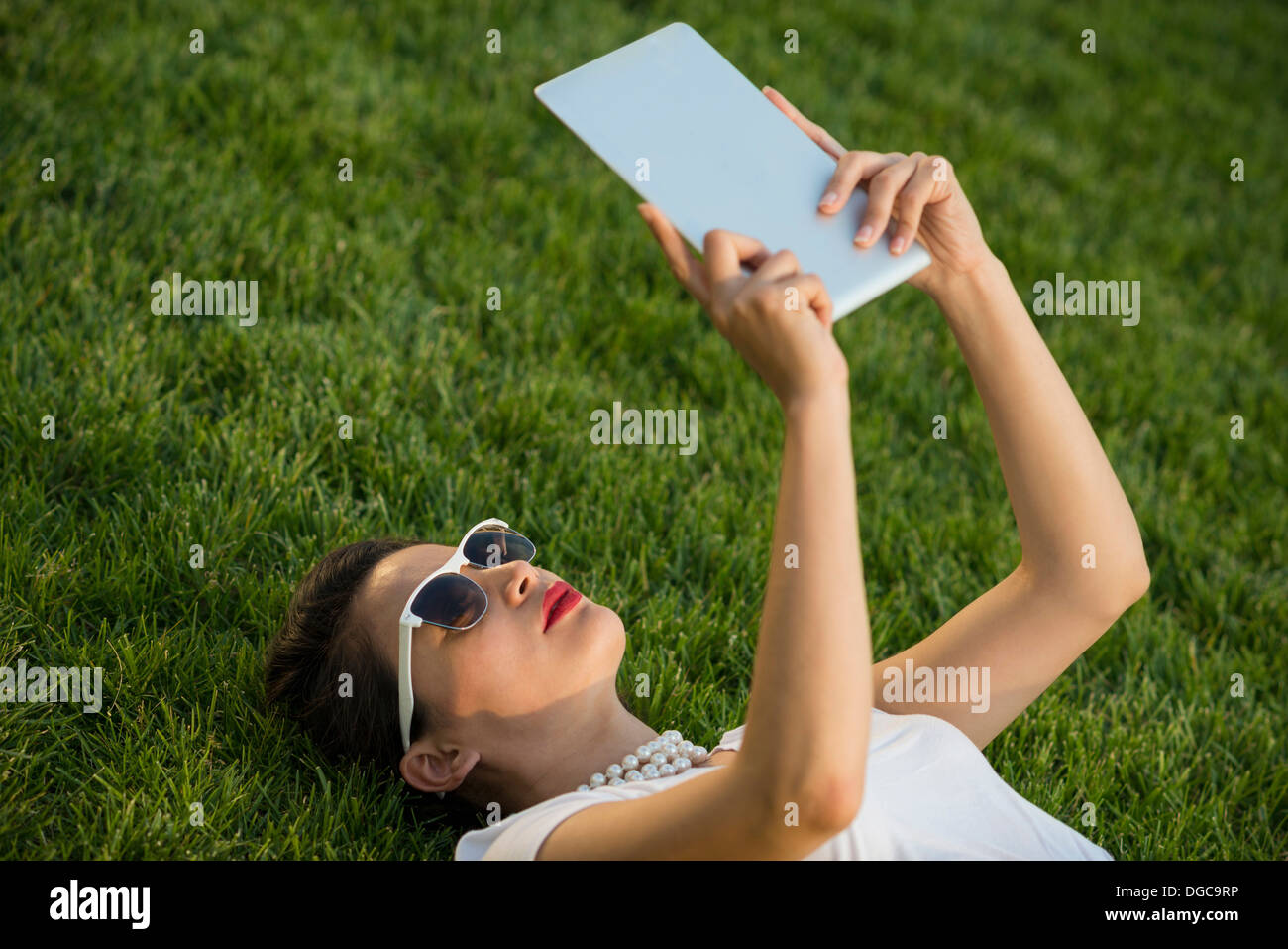 Woman lying in park using digital tablet Photo Stock