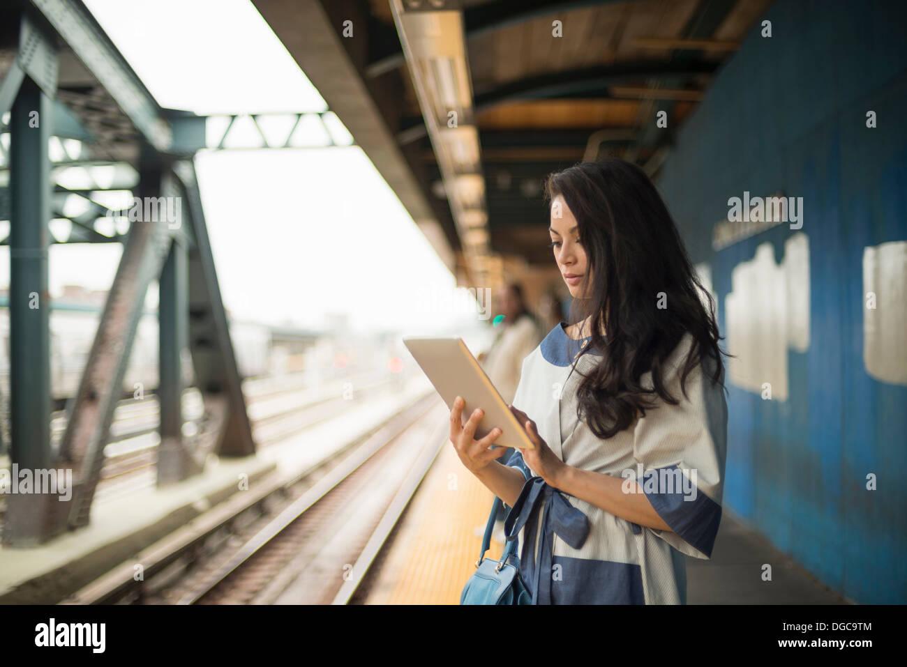 Woman using digital tablet sur plate-forme du métro, Brooklyn, New York Photo Stock
