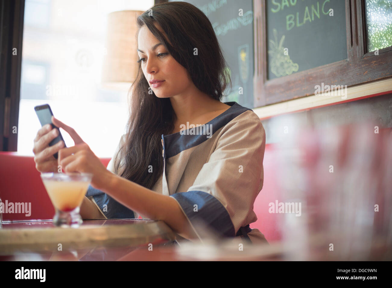 Mid adult women using mobile phone in restaurant Banque D'Images