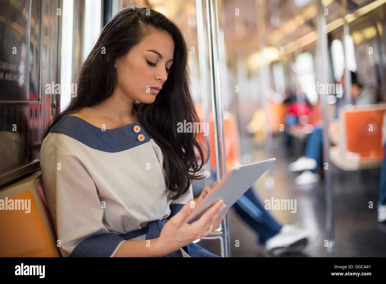 Woman using digital tablet on subway, New York Photo Stock