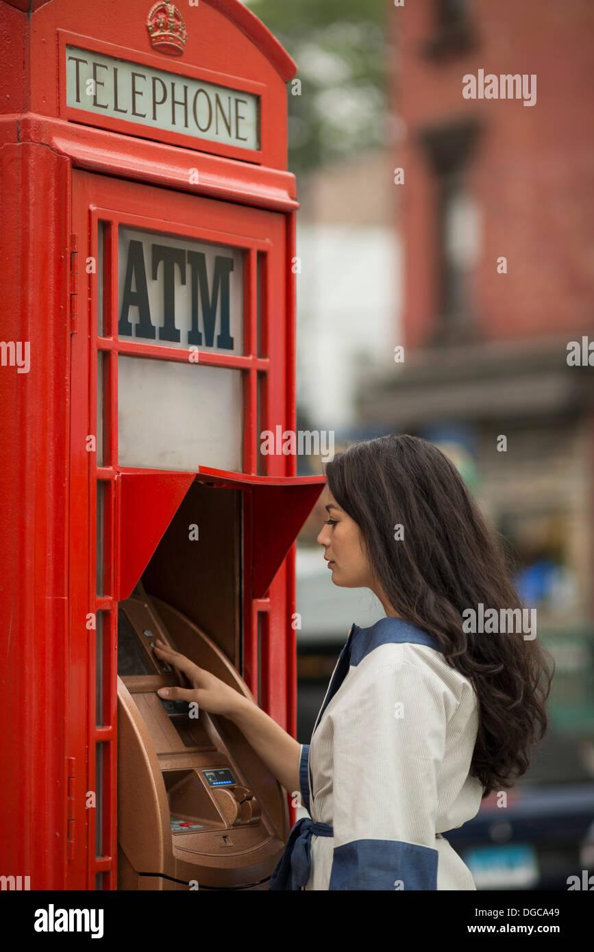 Les femmes adultes à l'aide d'espèces mi machine dans un téléphone public fort Photo Stock