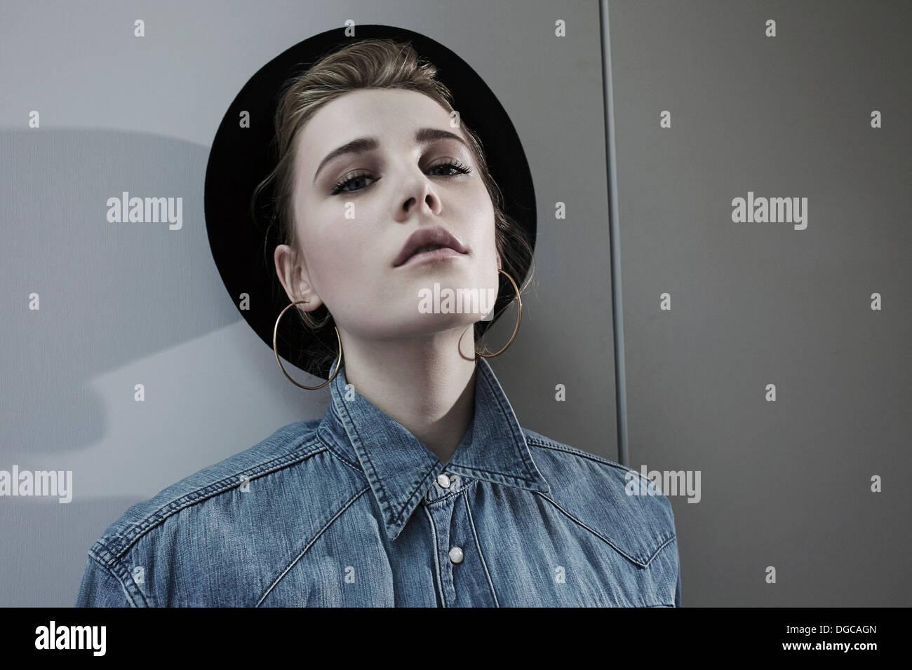 Young woman wearing hat et hoop earrings, portrait Photo Stock