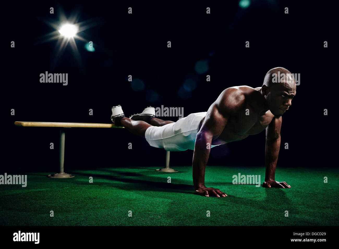Footballeur américain torse nu faisant press ups Photo Stock