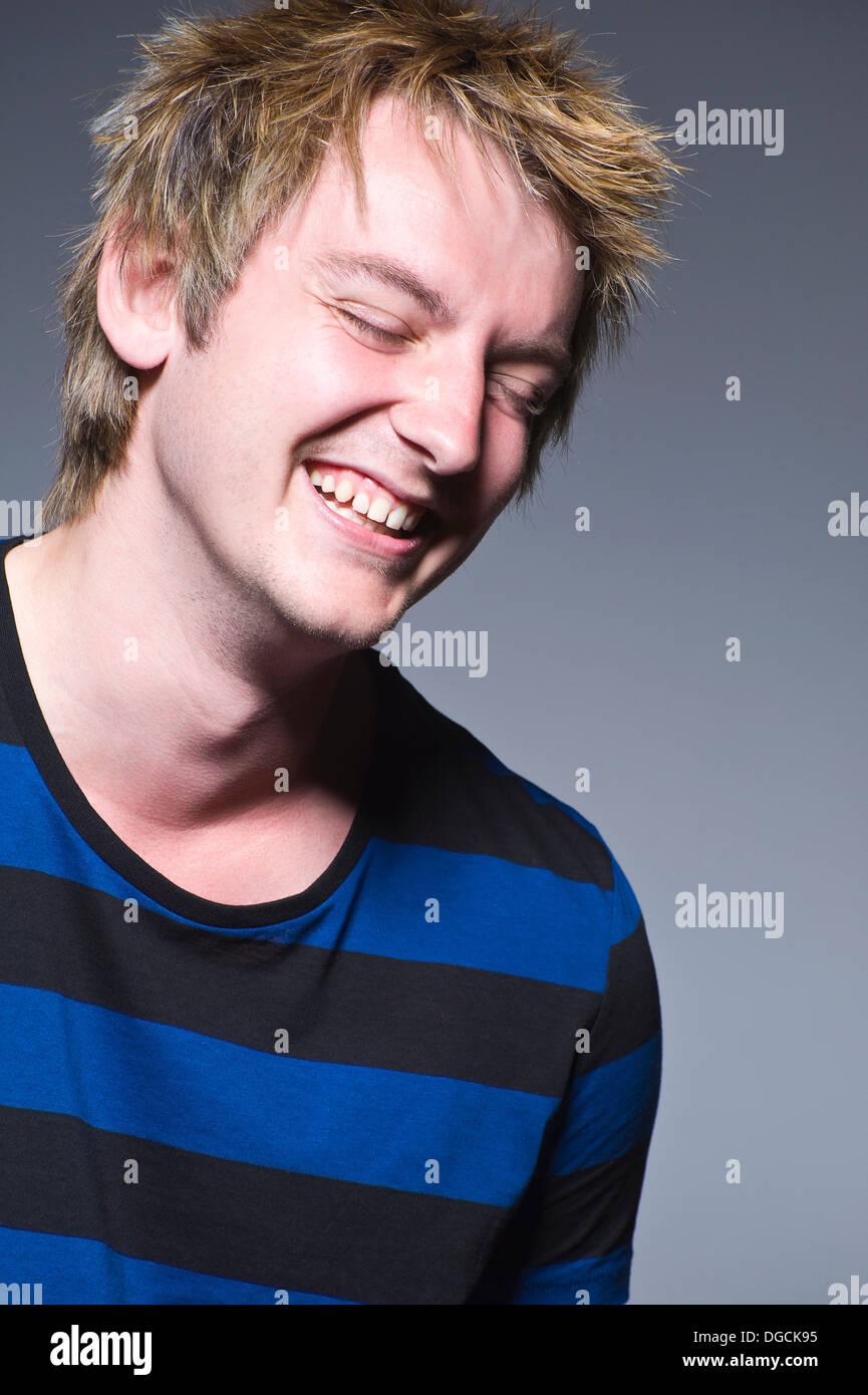 Jeune homme en t-shirt à rayures de rire, studio Photo Stock