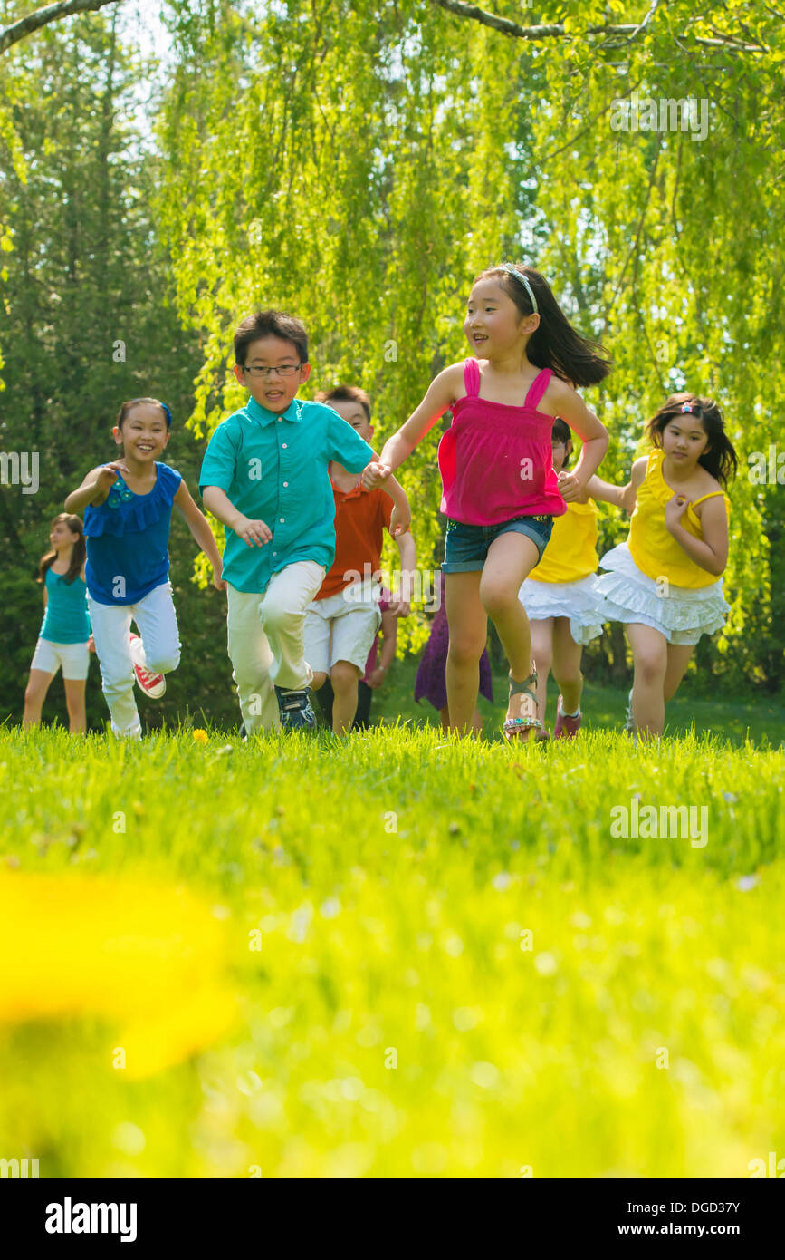 Children running on grass Photo Stock