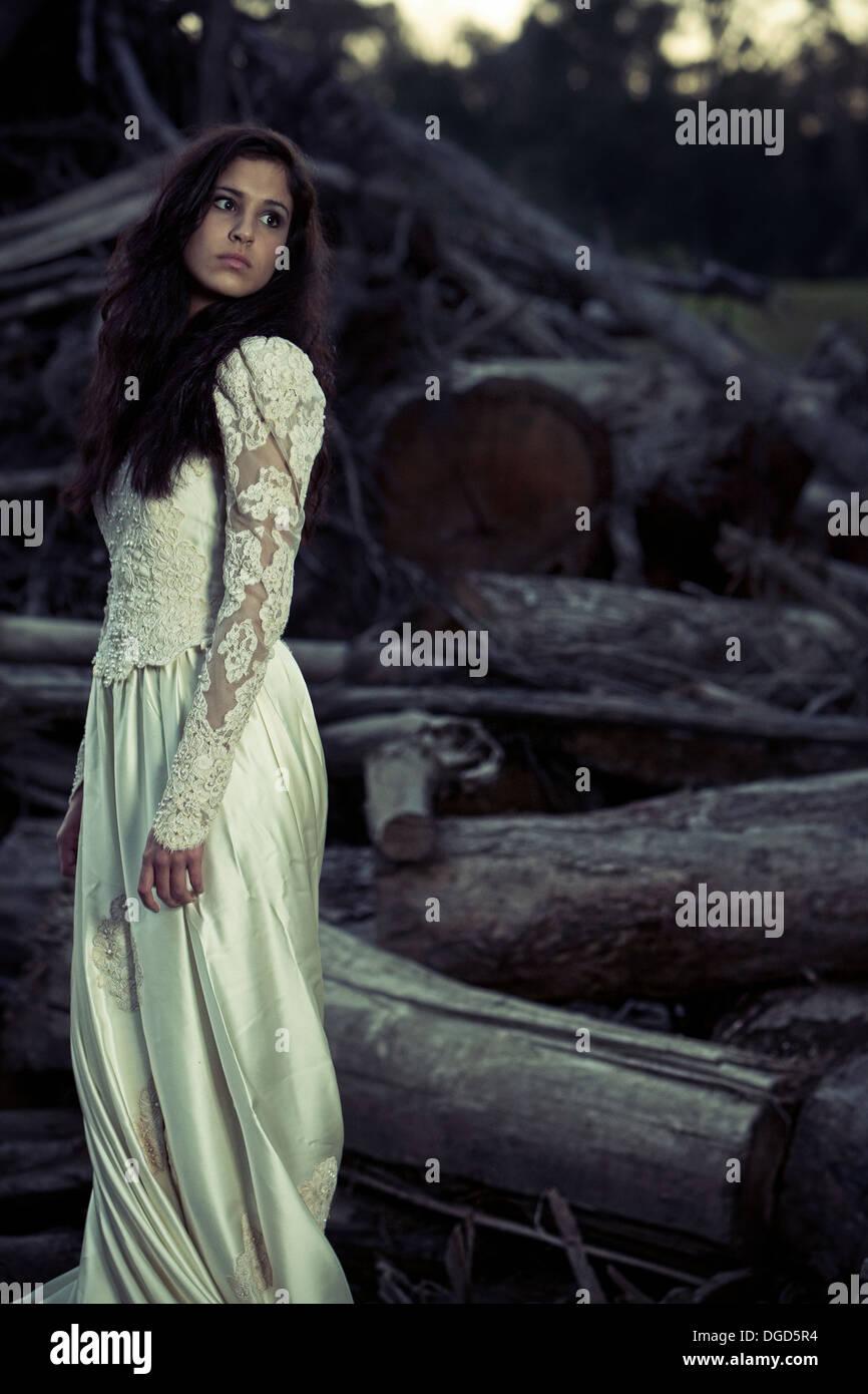 Femme en robe de mariage debout devant couper des arbres Photo Stock