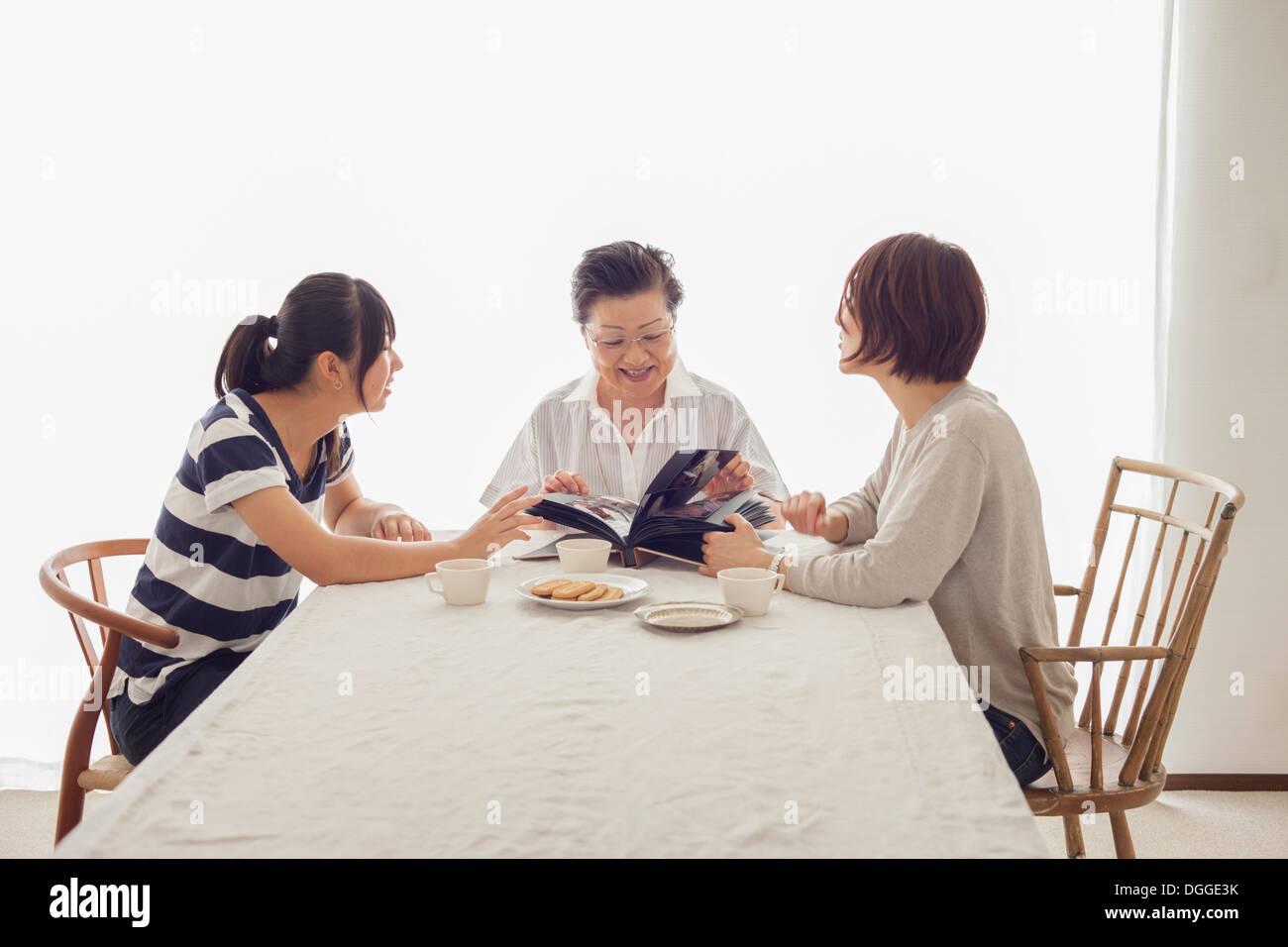 Three generation family looking at photograph album Photo Stock