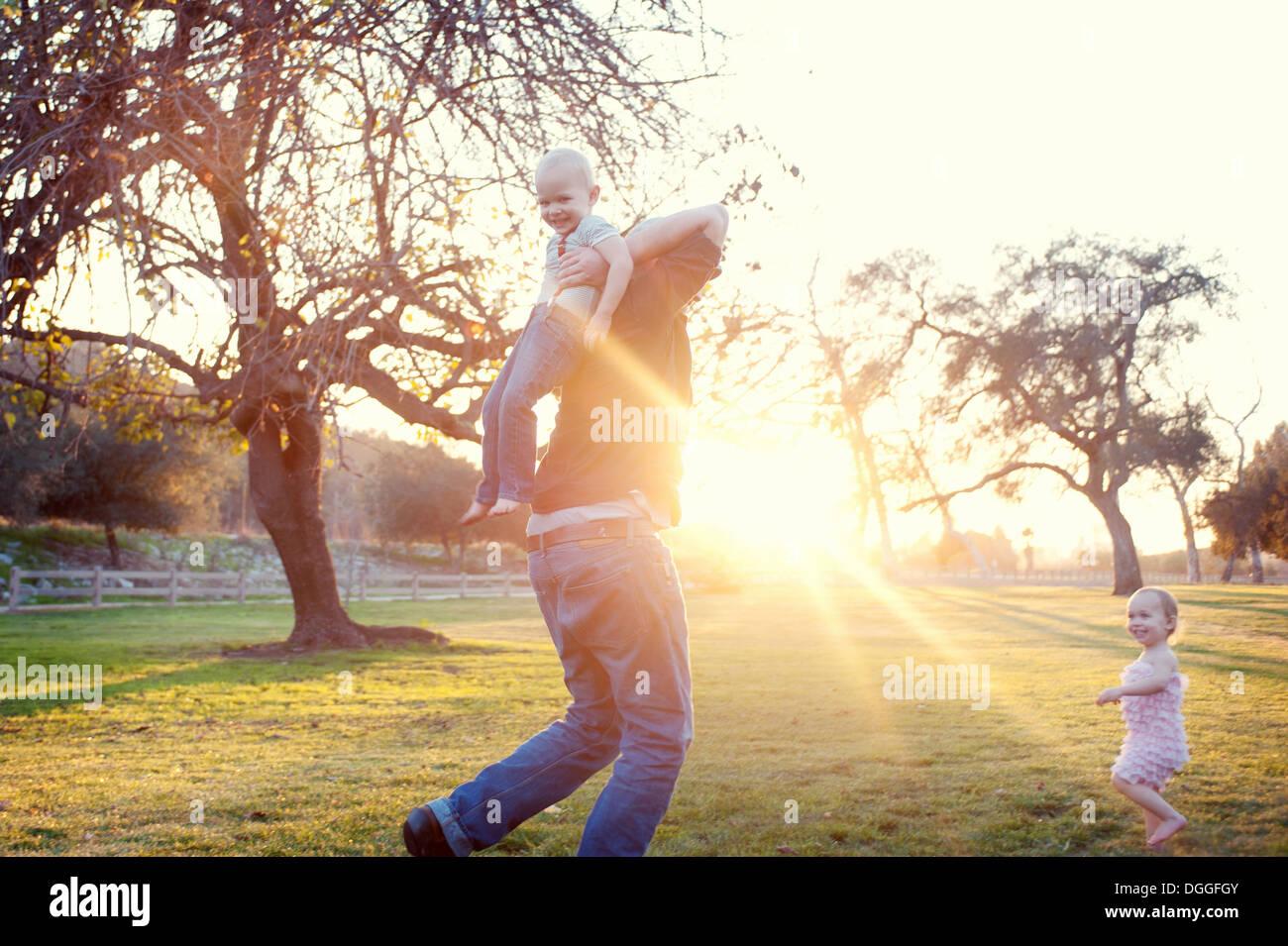 Père exerçant son fils en champ soleil Photo Stock