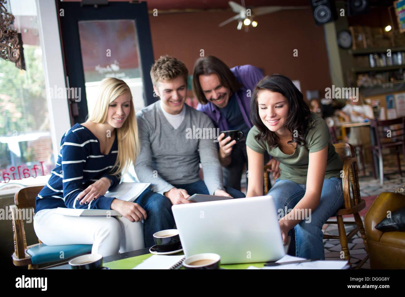 Groupe de personnes réunies autour de l'ordinateur in cafe Photo Stock