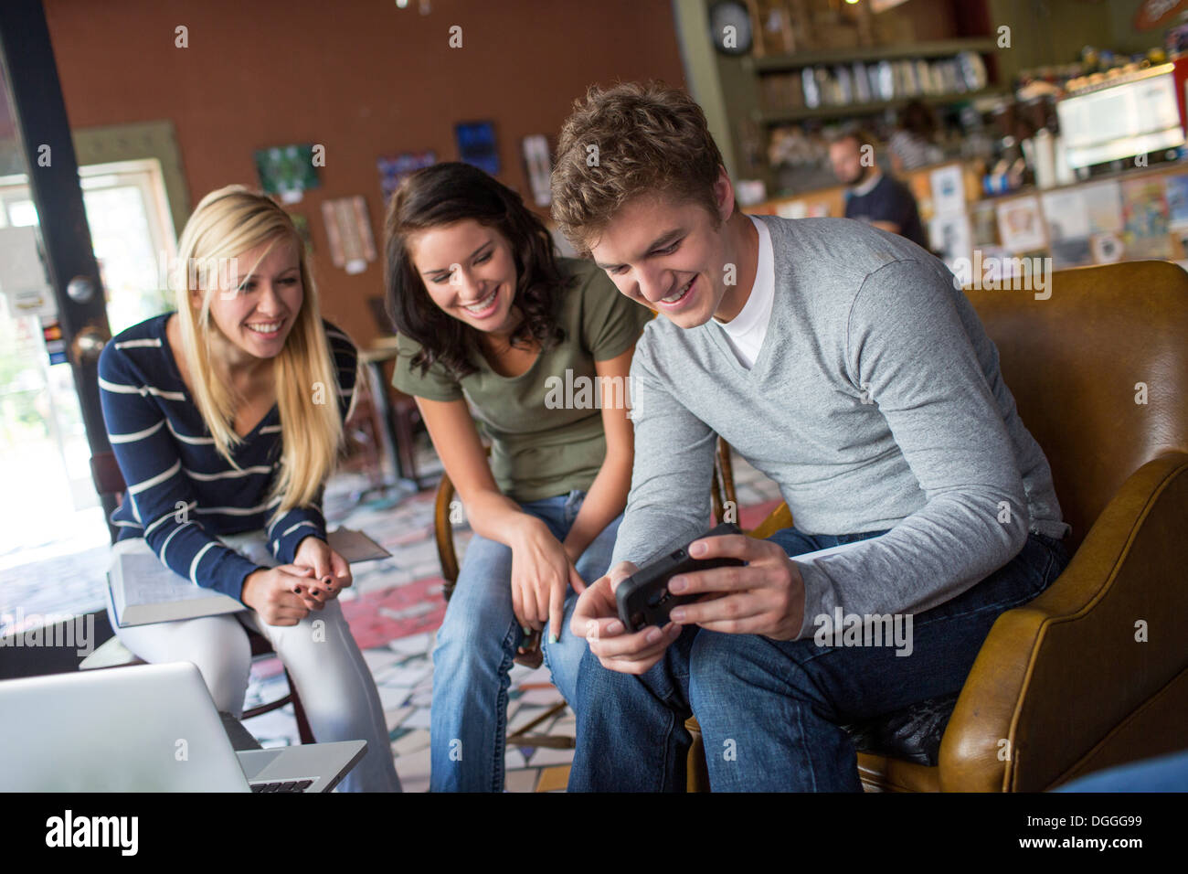 Petit groupe de personnes looking at smartphone in cafe Photo Stock