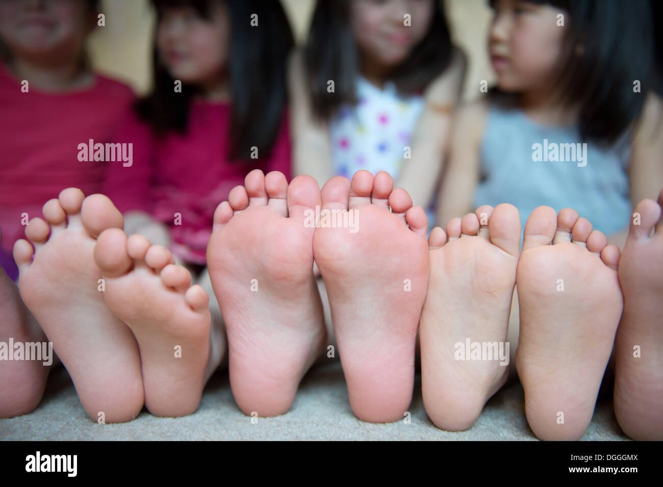 Les filles assis ensemble avec pieds nus dans une rangée Photo Stock