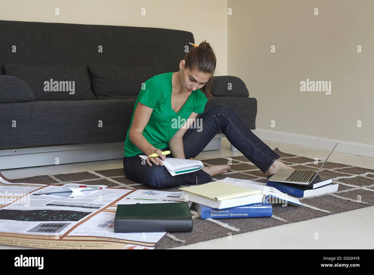Mid adult woman sitting on floor étudiant Banque D'Images