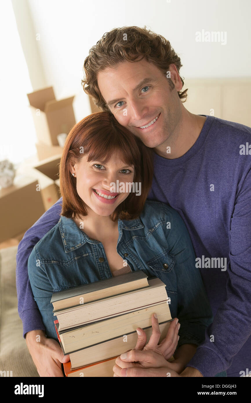 Couple holding pile of books Banque D'Images