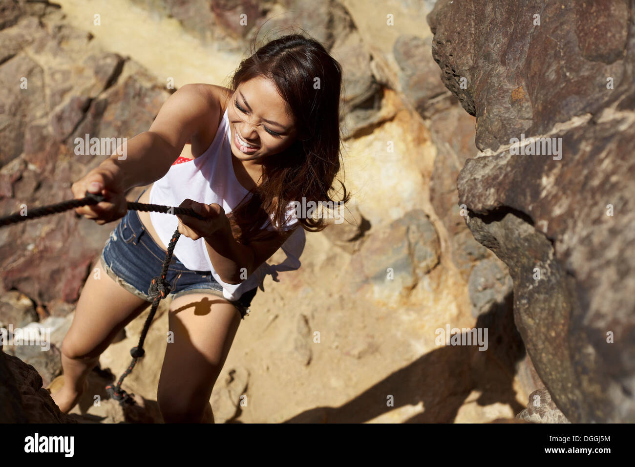 Jeune femme escalade rochers, Palos Verdes, California, USA Photo Stock